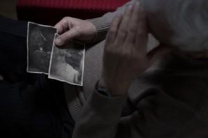 wydziedziczenie - staruszek ogląda zdjącia dzieci